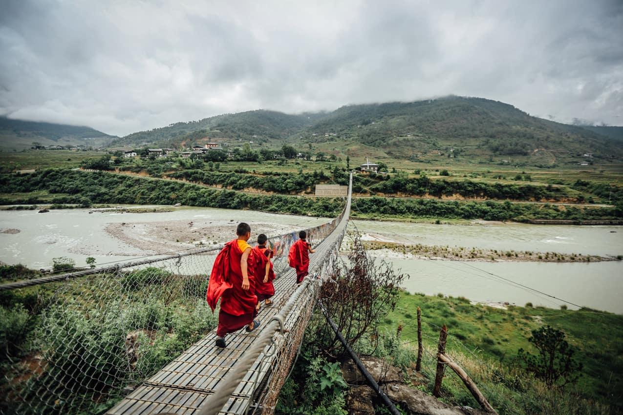 Monges atravessando ponte Butão